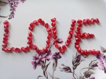 Beautiful red colour love letter using pomegranate seeds. royalty free stock image