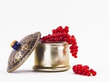 Beautiful red cranberries hanging over the edge of a luxury bowl. Closeup the open decorative bowl with patterned full delicious red cranberries over white royalty free stock photography