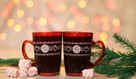 Beautiful red cups with coffee and marshmallow. Beautiful red cups with pattern ,hot drink coffee , tea with marshmallow near Christmas tree on a festive  bokeh Royalty Free Stock Image