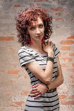 Beautiful red curly hair woman against brick wall Stock Photos