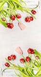 Beautiful red curved tulips with tags on white wooden background, top view, vertical floral border. Spring flowers Royalty Free Stock Photography