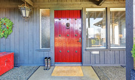 Beautiful red door and Christmas decor with grey wood house. Royalty Free Stock Photos