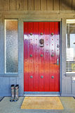 Beautiful red door and Christmas decor with grey wood house. royalty free stock images