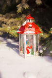 Beautiful red fairytale lantern on white snow near Christmas tree Royalty Free Stock Image