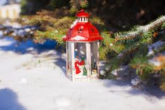 Beautiful red fairytale lantern on white snow near Christmas tree Royalty Free Stock Photography