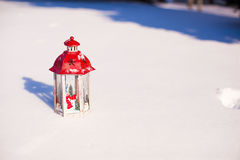 Beautiful red fairytale lantern on white snow near Christmas tree Royalty Free Stock Photos