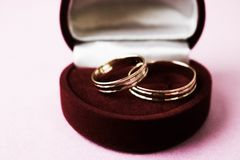 A beautiful red festive gift box velvet for two engagement, wedding rings with precious gold round precious pile rings. royalty free stock photos