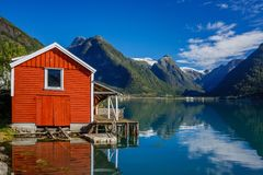 Beautiful red fishing house on fjord. Beautiful nature with blue sky, reflection in water and fishing house. Norway. Beautiful red fishing house on fjord stock images