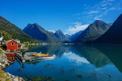Beautiful red fishing house on fjord. Beautiful nature with blue sky, reflection in water and fishing house. Norway. Beautiful red fishing house on fjord royalty free stock photography