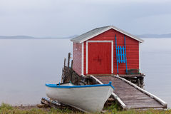 Red Newfoundland boat house NL Atlantic Canada. Beautiful red fishing shack and boat house also called stage at Newfoundland Atlantic ocean shore, NL, Canada stock photo