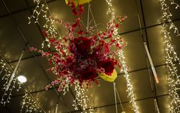 A beautiful red flower arrangement hanging from the roof. With amazing yellow lighting royalty free stock photos