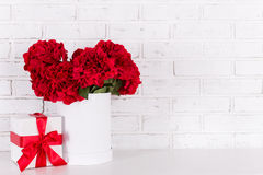 Beautiful red flowers and gift box over white brick wall Stock Images