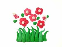 Beautiful bloom flower plasticine clay, red floral dough, green grass stock photos