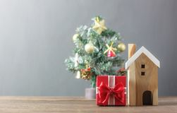 Beautiful red gift box and wooden white house.Blur background Christmas tree and decoration & ornament. Stock Photo