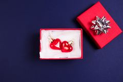 Beautiful red glass hearts in a red box on a dark blue background. Top view. Holidays concept royalty free stock images