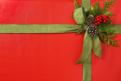 Beautiful red and green Christmas gift present with fabric ribbon bow and botanical decorations. Horizontal background border. Beautiful, classic red and green royalty free stock images