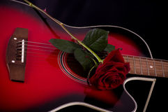 Beautiful red guitar with red roses. On black background Royalty Free Stock Images
