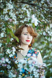 Beautiful red-hair girl. In a flowering apple orchard stock images