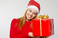 Beautiful red hair woman holding a big Christmas present. Stock Photo