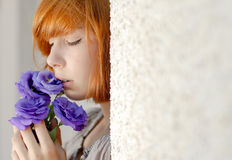 Beautiful red hair woman holding purple flower Stock Images