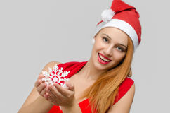 Beautiful red hair woman holding a snowflake. Royalty Free Stock Photo