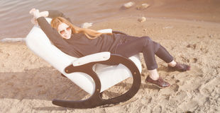 Beautiful red hair woman relax in chair on lake morning Royalty Free Stock Photo