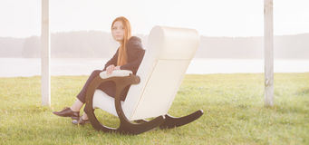 Beautiful red hair woman relax in chair on lake morning Royalty Free Stock Photography