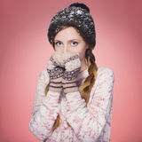 Beautiful red hair woman in winter outfit: warm sweater, scarf and hat with snow all over her. Isolated on pink red Royalty Free Stock Photos