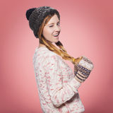 Beautiful red hair woman in winter outfit: warm sweater, scarf and hat with snow all over her. Isolated on pink red Stock Photos