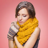 Beautiful red hair woman in winter outfit: warm sweater, scarf and hat with snow all over her. Isolated on pink red Royalty Free Stock Photography