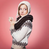 Beautiful red hair woman in winter outfit: warm sweater, scarf and hat with snow all over her. Isolated on pink red Royalty Free Stock Image