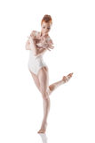 Beautiful red-haired ballerina dancing in studio Stock Photos