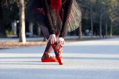 Beautiful red haired ballerina putting on her red pointe shoes at a park