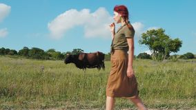 A beautiful red-haired country girl walks along a dirt road. stock footage