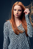 Beautiful red haired female in grey sweater Royalty Free Stock Photo