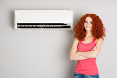 Beautiful red haired girl and air conditioner Stock Photos