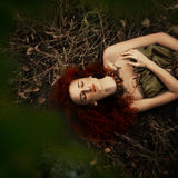 Beautiful red-haired girl in the apple orchard Royalty Free Stock Image