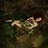 Beautiful red-haired girl in the apple orchard Royalty Free Stock Images