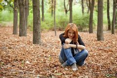 Beautiful red-haired girl in autumn park Royalty Free Stock Images