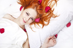 Beautiful red-haired girl in bed with rose petal. Stock Photos