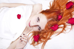 Beautiful red-haired girl in bed with rose petal. Royalty Free Stock Images