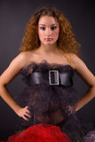 Beautiful red-haired girl in belt. Over gray background stock photography