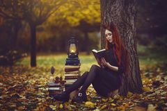 Beautiful red-haired girl with books and a lantern sitting under a tree in the autumn fairy forest. A fabulous autumn