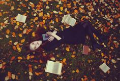 Beautiful red-haired girl with books lies on the grass in an autumn forest, top view. Autumn Fairytale photoshoot. stock photos