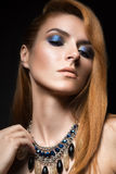 Beautiful red-haired girl with bright blue make-up and jewelry from natural stones. Beauty face. Stock Photos