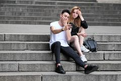 A beautiful red haired girl and a brunette guy saw something interesting in their mobile phone stock images