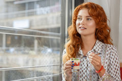 Beautiful red-haired girl in cafe Royalty Free Stock Photos