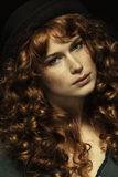 Beautiful red-haired girl with curls, black hat Stock Images