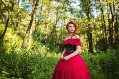 Beautiful red-haired girl in a red dress on a green background Royalty Free Stock Photography