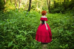 Beautiful red-haired girl in a red dress on a green background Stock Photography